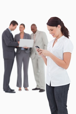 Saleswoman with mobile phone and colleagues behind her against a white background photo