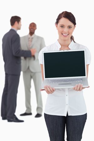 Businesswoman showing laptop with colleagues behind her against a white background photo