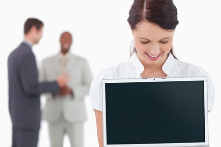 Businesswoman showing laptop with associates behind her against a white background Stock Photo - 13607204