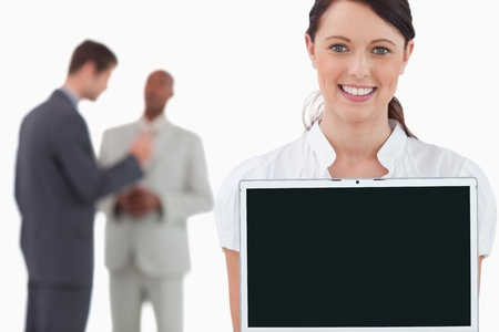 Tradeswoman showing laptop with colleagues behind her against a white background photo