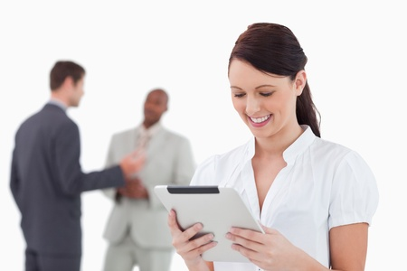 Tradeswoman with tablet and colleagues behind her against a white background Stock Photo - 13605889
