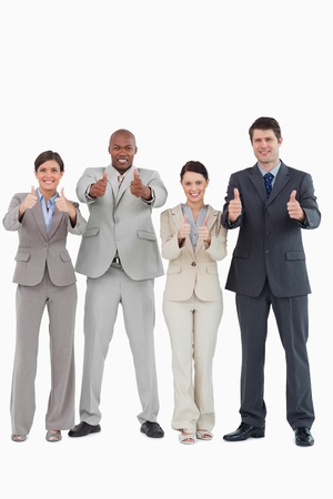 Businessteam giving thumbs up together against a white background photo