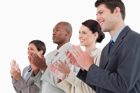 Side view of applauding businessteam standing together against a white background photo