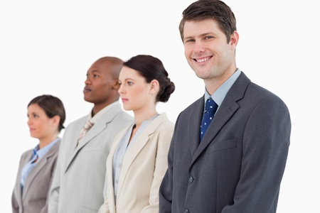 Smiling businessman standing next to his team against a white background Stock Photo - 13609413