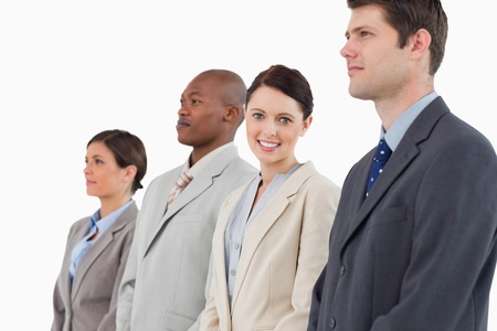 Smiling businesswoman standing between her colleagues against a white background Stock Photo - 13609638