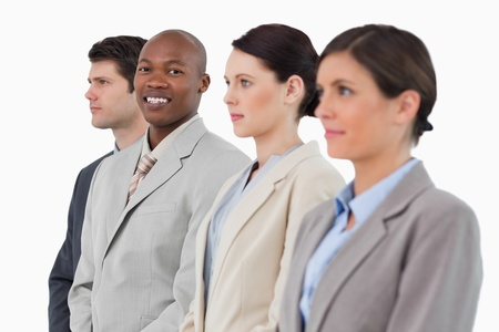 Smiling salesman standing between his associates against a white background Stock Photo - 13615138