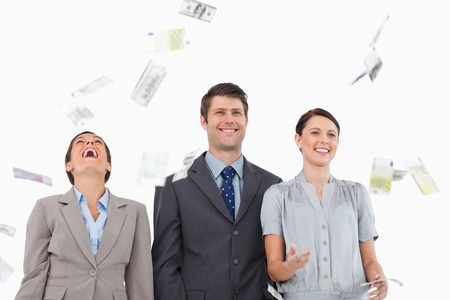 Money falling down on smiling salesteam against a white background photo