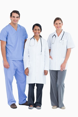Smiling young medical staff standing together against a white background photo