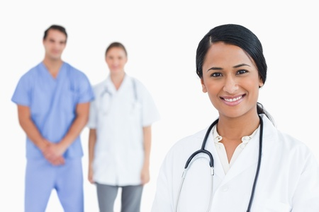 Smiling doctor with colleagues behind her against a white background photo