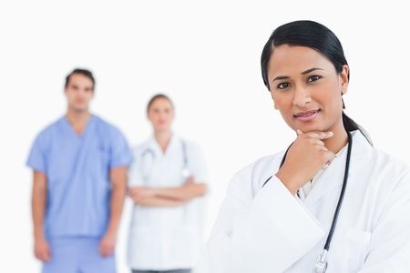 Thoughtful doctor with colleagues behind her against a white background Stock Photo - 13604440