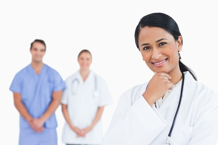 Smiling doctor in thinkers pose with colleagues behind her against a white background photo