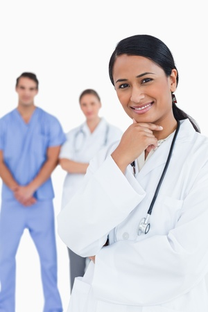 Smiling doctor with staff behind her against a white background Stock Photo - 13607132