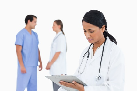 Doctor taking notes with talking staff members behind her against a white background photo