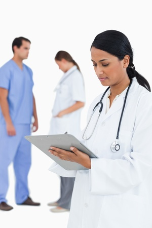 doctor taking notes with staff members behind her against a white background photo