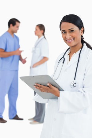 Smiling doctor with clipboard and staff members behind her against a white background photo