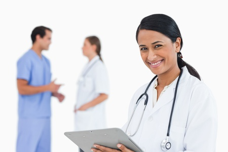Smiling doctor with clipboard and colleagues behind her against a white background photo