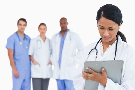 Female doctor taking notes on clipboard with staff members behind her against a white background photo