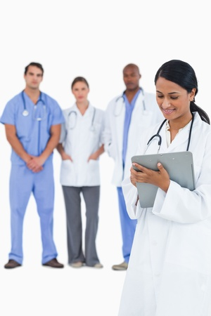 Female doctor taking notes with staff members behind her against a white background photo