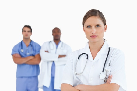 Female doctor with folded arms and male colleagues behind her against a white background photo