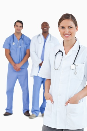 Smiling female doctor with male colleagues behind her against a white background photo