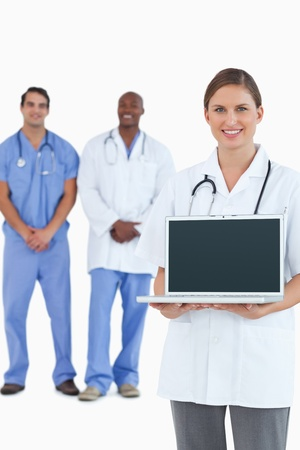 Smiling doctor showing laptop with colleagues behind her against a white background photo