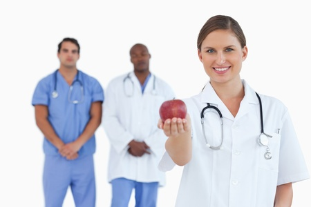 Doctor offering apple with colleagues behind her against a white background photo