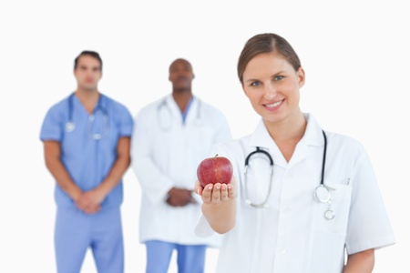 Smiling doctor offering apple with colleagues behind her against a white background photo
