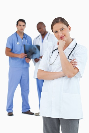 thinkers: Doctor in thinkers pose with colleagues behind her against a white background