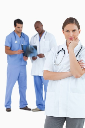 Thinking doctor with colleagues behind her against a white background Stock Photo - 13606744