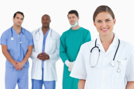 Female doctor with colleagues behind her against a white background photo