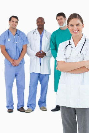 Smiling doctor with folded arms and colleagues behind her against a white background photo