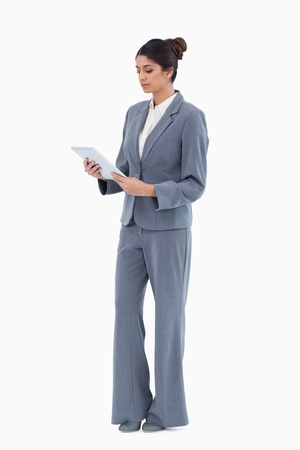 Businesswoman looking at tablet against a white background photo
