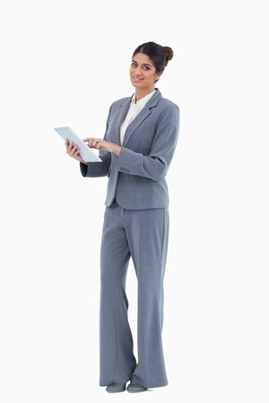 Smiling saleswoman using tablet against a white background photo