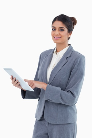 Smiling saleswoman using tablet computer against a white background photo