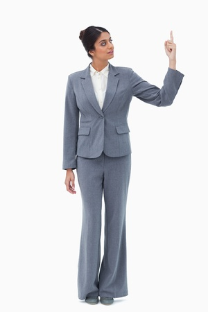 Saleswoman pointing up against a white background Stock Photo - 13605892