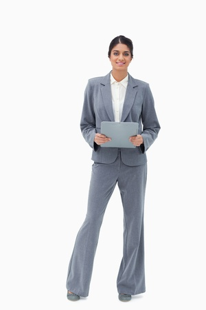 Smiling businesswoman holding clipboard against a white background photo
