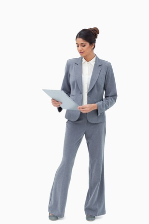 Businesswoman looking at her clipboard against a white background photo