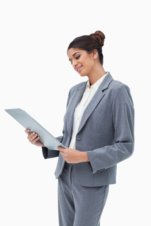 Smiling businesswoman looking at clipboard against a white background photo
