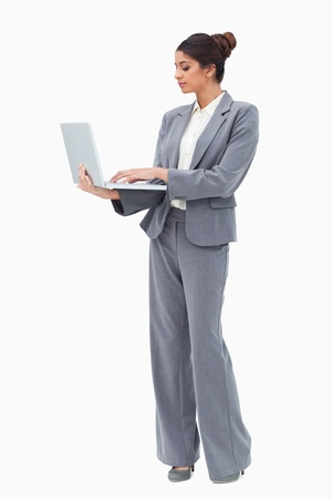 Businesswoman using laptop while standing against a white background photo