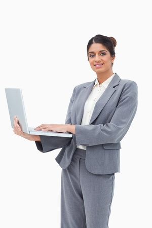 Smiling businesswoman using notebook while standing against a white background photo