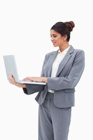 Smiling businesswoman using her laptop white standing against a white background photo