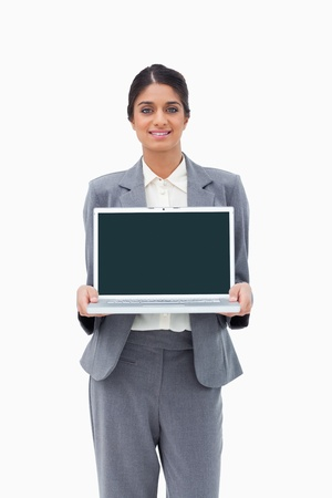 Smiling businesswoman showing her laptop against a white background photo