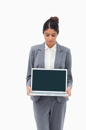 Businesswoman looking at laptop in her hands against a white background photo
