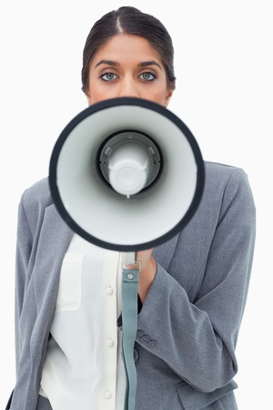 Businesswoman using megaphone against a white background photo