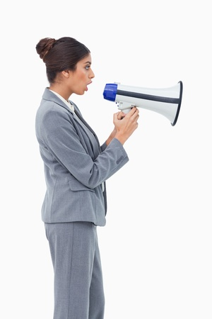 Side view of businesswoman using megaphone against a white background photo