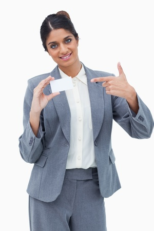 Smiling saleswoman pointing at blank business card against a white background Stock Photo - 13616090