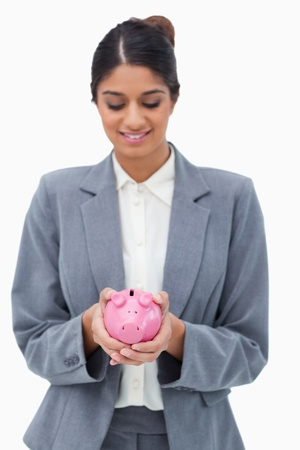 Smiling bank employee looking at piggy bank in her hands against a white background photo