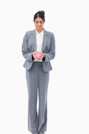 Smiling bank assistant with piggy bank against a white background Stock Photo - 13601328