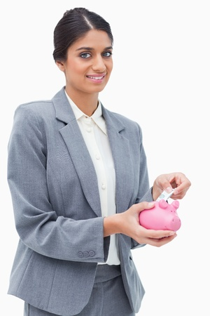 Smiling bank assistant putting money into piggy bank against a white background photo