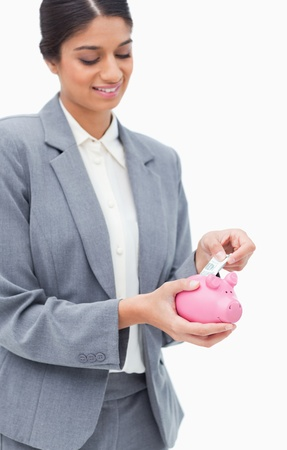 Smiling bank employee putting bank note into piggy bank against a white background Stock Photo - 13606124